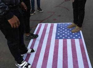 تصویر لگدمال کردن پرچم آمریکا در تظاهرات مردم عراق در بغداد