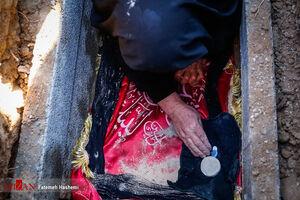عکس/ مادر شهید طارمی فرزندش را داخل قبر گذاشت