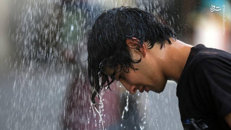 2877398 - عکس/ دوش خیابانی برای مقابله با گرما