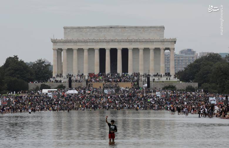 """یک معترض به تبعیض نژادی در برابر بنای یادبود """"ابراهام لینکلن"""" دست خود را مشت کرده است /عکس: رویترز"""