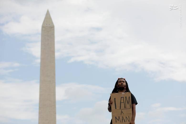 مردی با دست نوشته مرتبط به زندگی سیاهان/ عکس: رویترز