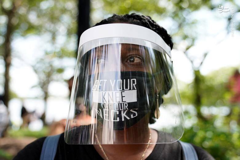"""یک زن کالیفرنیایی با پوشش ماسک در تظاهرات """"زانویت را از گردنم بردار"""" /عکس: رویترز"""