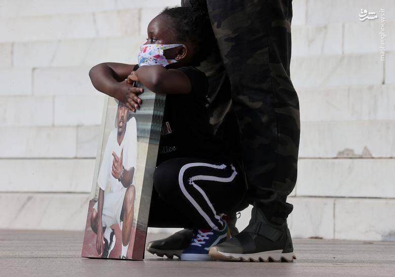 """دختر 4 ساله """"مارکیس الستون"""" که در تاریخ 12 ژوئن 2018 توسط پلیس واشنگتن کشته شد، عکسی از پدرش در بنای یادبود لینکلن در دست دارد/ عکس: رویترز"""