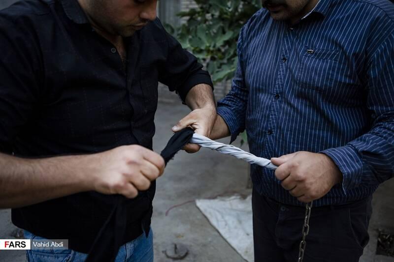 دور پیچ کردن پارچه به زنجیر برای جلوگیری از سوزش دست -آئین مذهبی پولکه پرانی