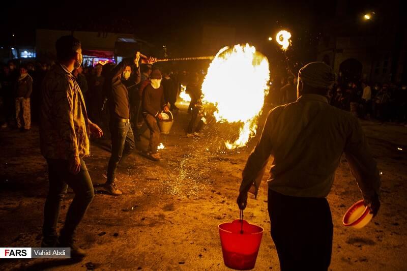 افرادی که سطل آب در دست دارند برای جلوگیری از سوختگی افراد آب می پاشند-آئین مذهبی پولکه پرانی