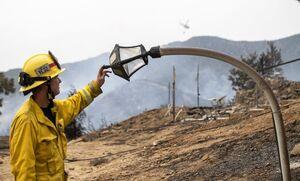 عکس/ خم شدن تیر چراغ برق در آتش سوزی کالیفرنیا