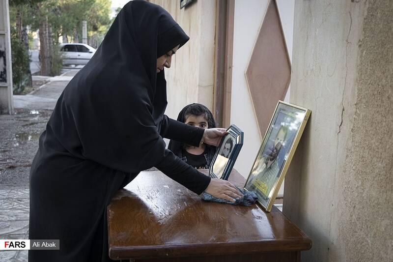 عروس خانه در حال قرار دادن تمثال مبارک شهید جلوی در خانه