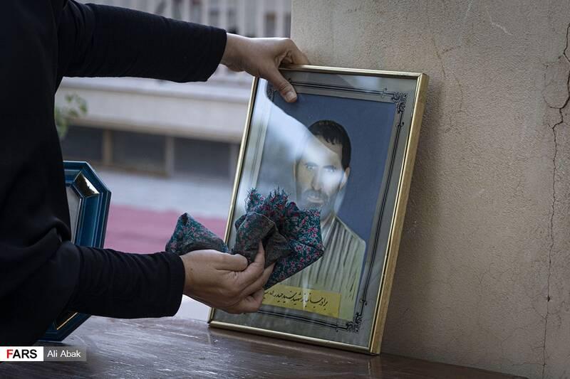 عروس خانه در حال غبارروبی تمثال مبارک شهید جلوی در خانه