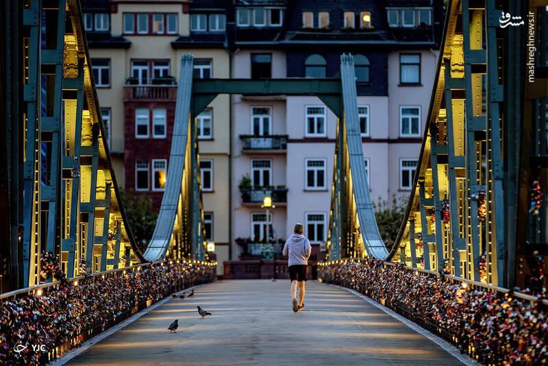 عبور یک مرد از پل عابر پیاده آیزرنر استگ بر روی رودخانه اصلی در فرانکفورت، آلمان