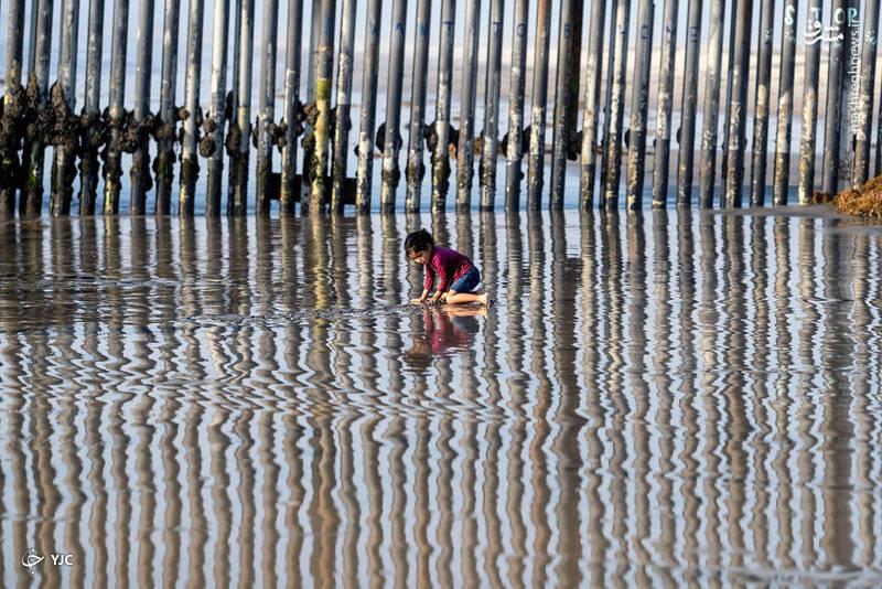 دختری در ساحل نزدیک مرز ایالات متحده و مکزیک، در تیجوآنا، مکزیک بازی می کند