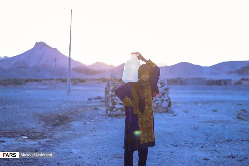 دختری از اهالی روستا که به دلیل نبود لولهکشی، آب را از قنات به خانه می برد.