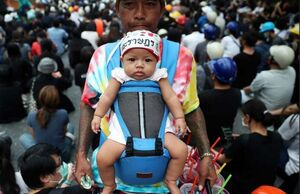 عکس/ کاسبی پدر با همراهی نوزادش در میان معترضین