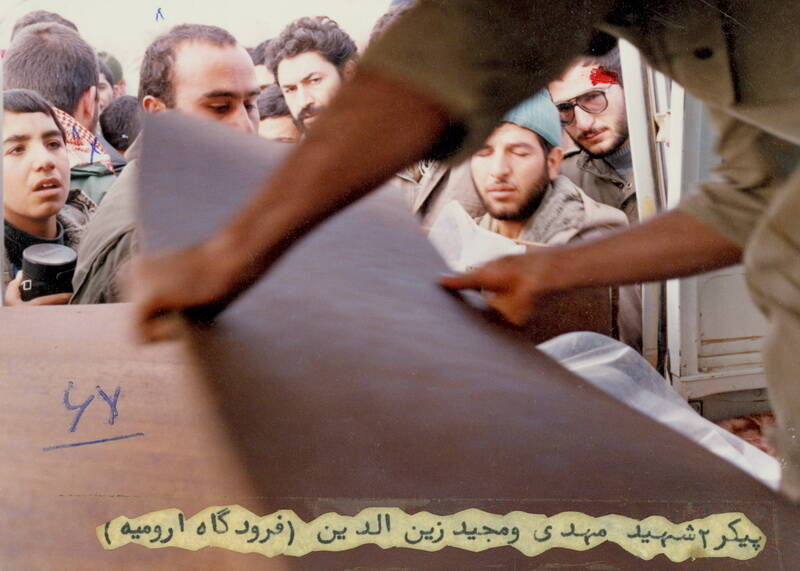 شهید حمید احدی هنگام آخرین وداع با پیکر شهید مهدی زین الدین