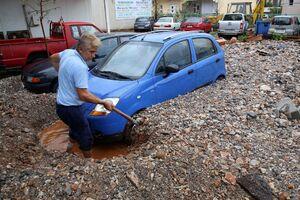 مردی در حال بیرون کشیدن ماشینش بعد از باران شدید در یونان