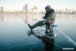 عکس/ ماهیگیری از زیر یخ قطور سطح دریاچه