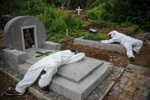 استراحت کارمندان گورستانی در باندونگ اندونزی پس از دفن یک فوتی کرونا/ رویترز