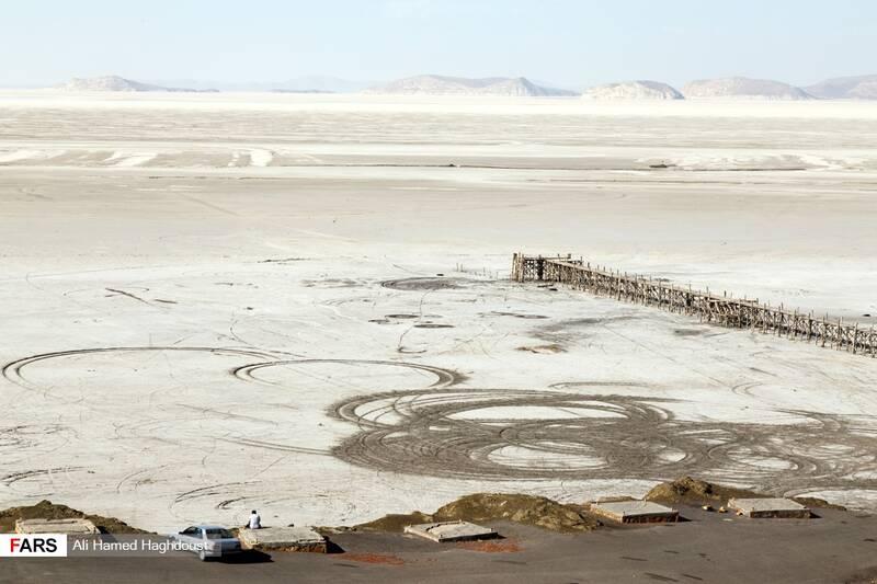 مردی در کنار اتومبیل خود بر روی کف سیمانی که در گذشته آلاچیق بودند نشسته و دریاچه خشکیده ارومیه در بندر رحمانلو را تماشا میکند.