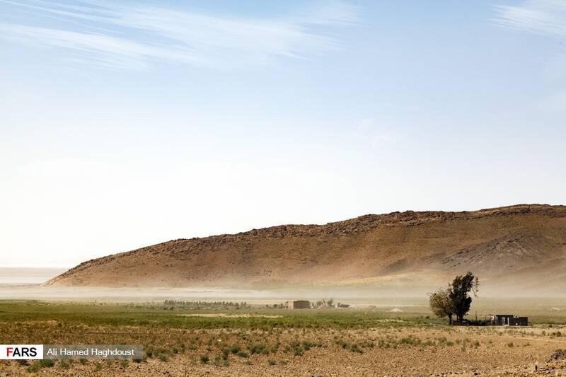 بخشهایی از زمینهای خشک شده و چاههای آب در اطراف دریاچه ارومیه در نزدیکی بندر رحمانلو دیده میشود. طوفان نمک از کف دریاچه بر هوا برخاسته است.