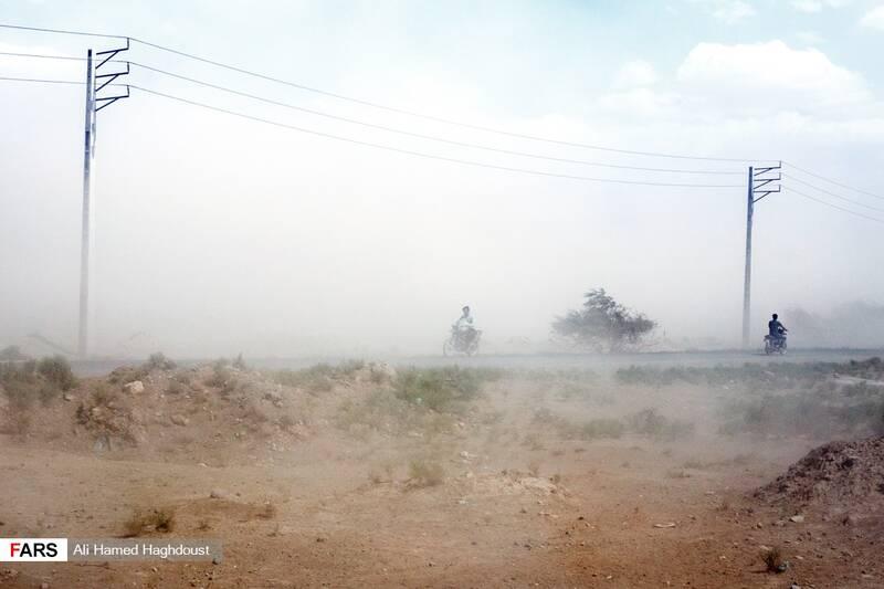 مردان موتورسوار در حال عبور از بین طوفان نمک و گرد و خاک در نزدیکی شهر عجبشیر هستند.
