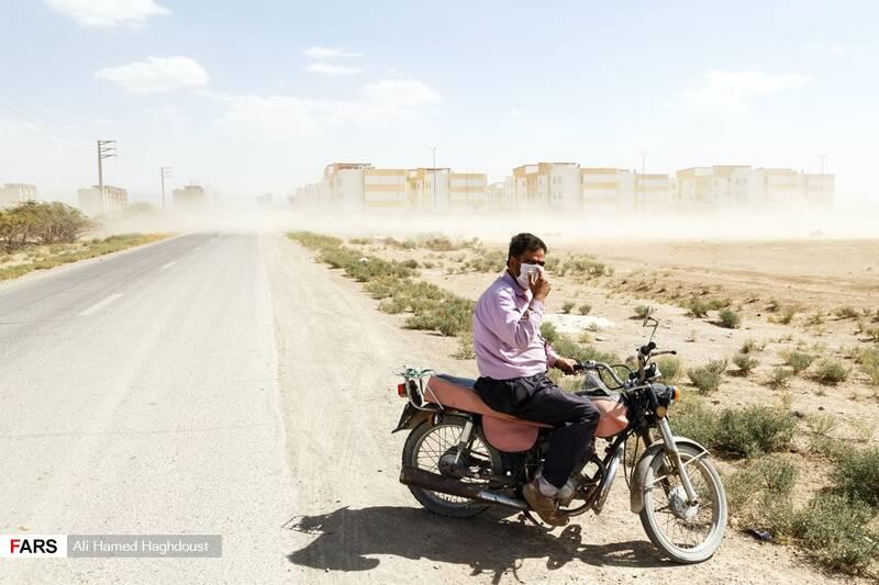 مرد موتورسوار برای حفاظت خود از ذرات طوفان نمک و گرد و خاک معلق در هوا و بیماری کرونا از ماسک استفاده میکند.