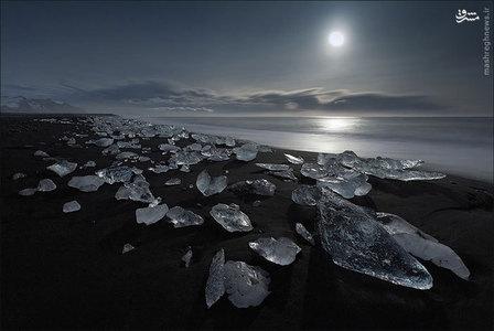 شن و ماسه سیاه این ساحل در ایسلند در تضاد زیبایی با تکه های سفید و شیشه ای یخ است.
