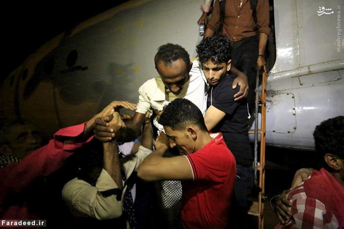 مردم در حال کمک به مجروحان یمنی برای پیاده شدن از هواپیما و انتقال به بیمارستان در