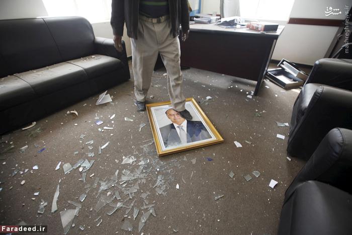 مردی پس از بمباران هوایی صنعا روی قاب عکس