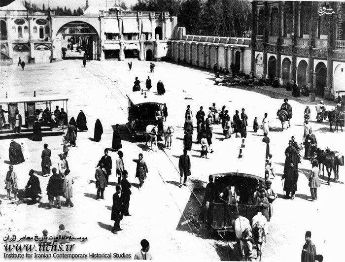دروازه خیابان لالهزار در بخش شمال شرقی میدان توپخانه، نمای بانک شاهی در سمت راست و محل تقاطع حرکت واگن اسبیها از خیابانهای چراغ برق، لالهزار و مریضخانه. ازدحام عابران پیاده از هر نوع و گوسفندانی در کنار ساختمان بانک