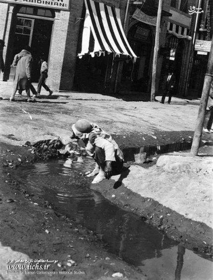 نظافت کارگری در جوی رو باز و خانمی در لباس فرنگی در بالای تصویر