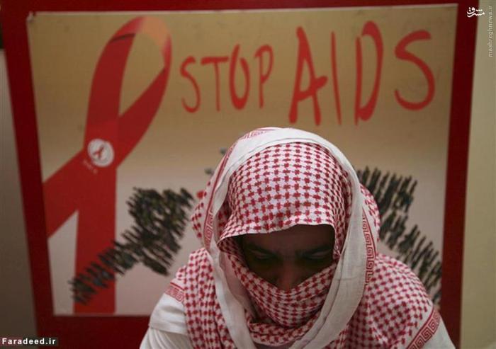مرد مبتلا به بیماری ایدز که صورت خود را پوشانده در یک انجمن خیریه کمک به بیماران مبتلا به ایدز نشسته است