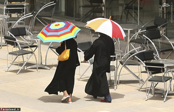دو زن در حال عبور از کنار یک کافی شاپ در ریاض