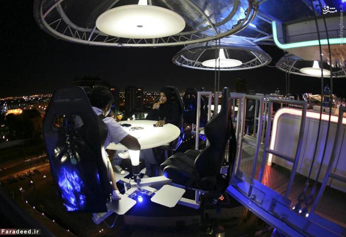 زن عرب و همسرش در رستوران معلق در جده؛ این رستوران در جده با کمک جرثقیل میزهای غذا و میهمانان را در فضایی معلق میان زمین و آسمان نگه میدارد