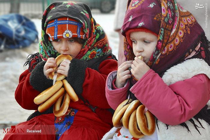 دو بچه روس با لباس سنتی روسی در حال خوردن نان