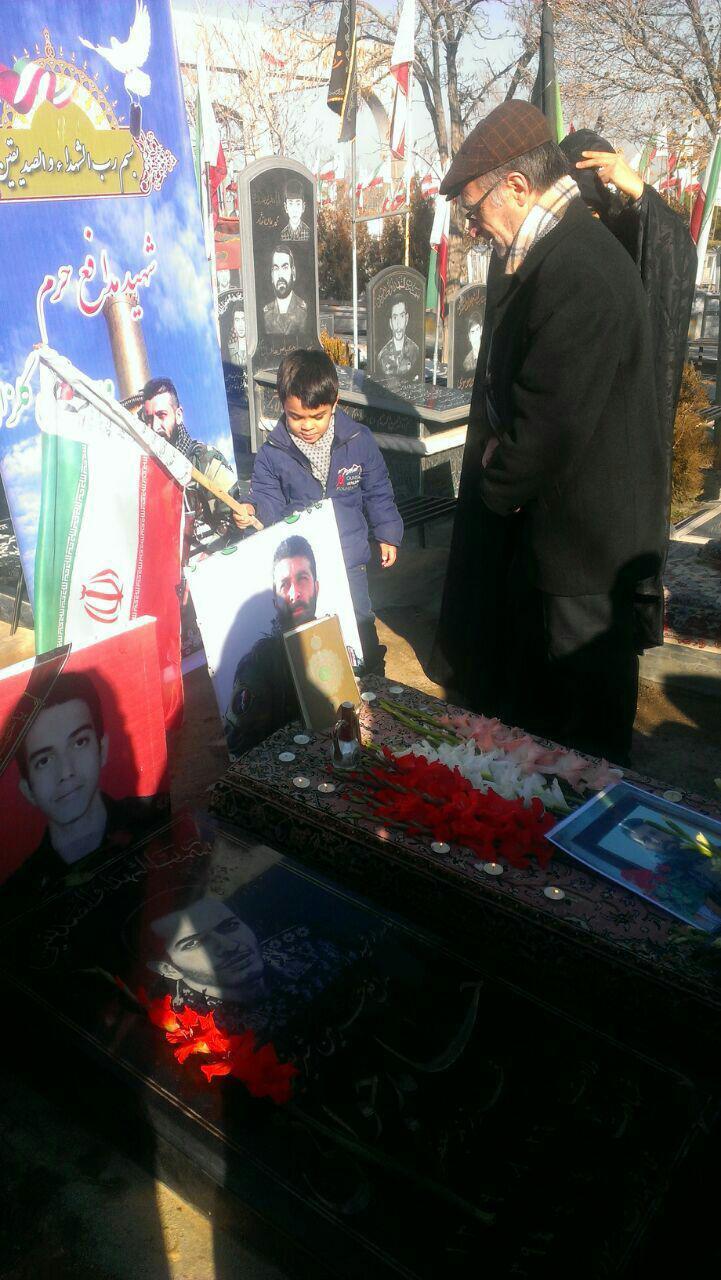 عکس/فرزند شهید مدافع حرم بر سر مزار پدر