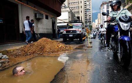 تلاش یک کارگر برای تعمیر لوله آب در کاراکاس – پایتخت ونزوئلا – 26 سپتامبر 2012