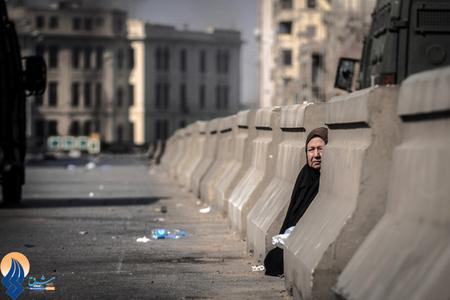 پناه گرفتن یک زن در پی تیراندازی سربازان ارتش مصر در خیابانهای قاهره