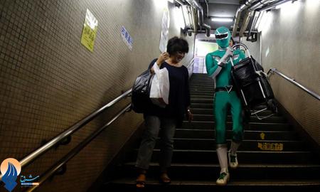 مردی که با پوشیدن لباسی عجیب شبیه به لباس قهرمانان فیلمهای هالیودی،به سالمندان در سطح شهر توکیو در جابه جایی وسایل سنگین به آنها کمک میکند _ ژاپن