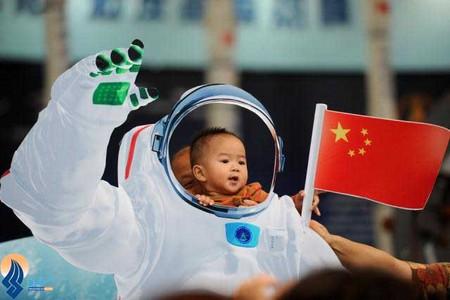 عکس یادگاری یک کودک با لباس فضانوردی در نمایشگاه فناوری پکن