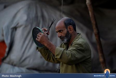 یک کارگر پاکستانی در حال کوتاه کردن موهای خود