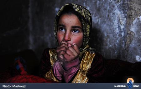 تلاش کودک افغان برای گرم کردن خود