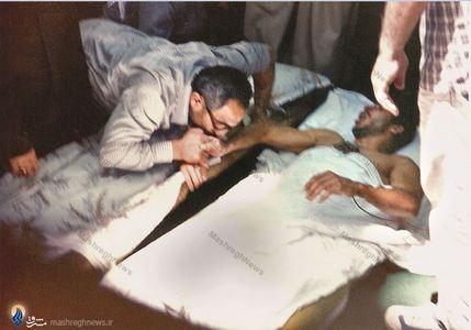 شهید سید اسدالله لاجوردی درحال بوسیدن دست یک جانباز