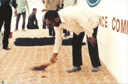 شهید سید اسدالله لاجوردی در حال جارو کردن حسینیه زندان اوین