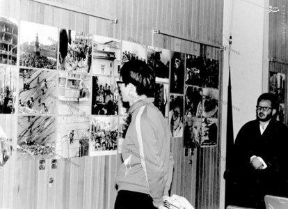 شهید سید عبدالکریم هاشمی نژاد در بازدید از یکی از نمایشگاههای عکس انقلاب