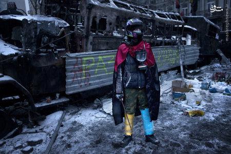معترض اوکراینی در کنار ماشین سوخته پلیس ضد شورش
