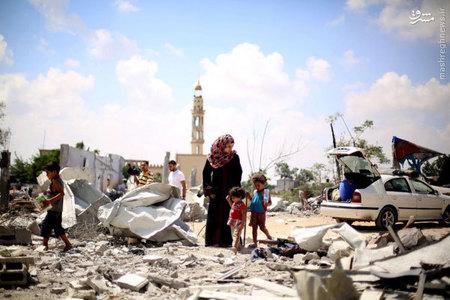 قدم زدن زن فلسطيني بر آوارهاي به جاي مانده از حملات اسرائيلي به غزه