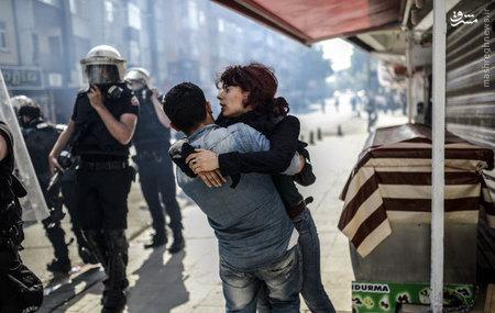 مردي در حال كمك به همسرش پس از درگيري بين كردها و پليس در استانبول