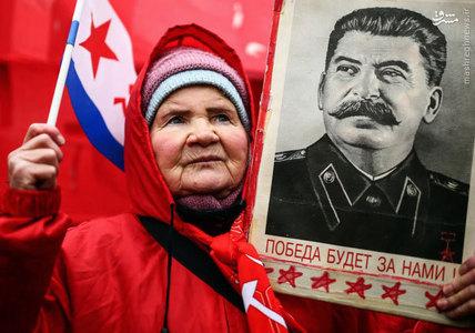 يك زن روس در حالي كه تصويري از جوزف استالين را در دست دارد در مراسم