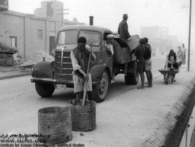 کامیونت خدمات عمومی در طهران قدیم در حالی که کارگران به روش قاجاری و بدون امکانات اولیه و حتی کفش به کارگری مشغولند