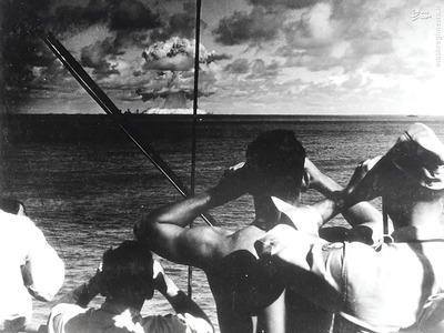 نظامیان آمریکایی در حال تماشای انفجار یک آزمایش هسته ای که در جزیره مرجانی بیکینی در 25 جولای 1946 انجام شد. پس از دو تست دیگر و دو بمبی که در هیروشیما و ناکازاکی منفجر شد، این آزمایش پنجمین انفجار هسته ای تا آن زمان بود .