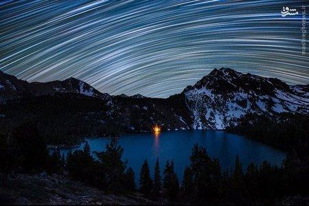 * ردپای ستارگان بر فراز دریاچه سبز _  ردپای ستارگان؛ آسمان کمپی که با آتش در کنار دریاچه ای سبز در Hoover Wilderness ایالت کالیفرنیا روشن شده را چراغانی کرده است.
